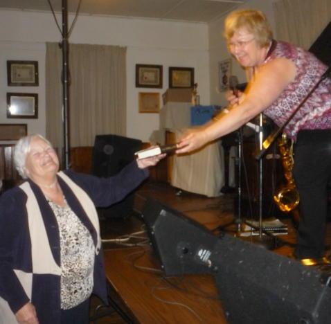 Pauline Clark hands Bernice Walker a copy of The Dwelling